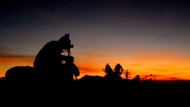 Silhouette : panning photographers on peak of mountain