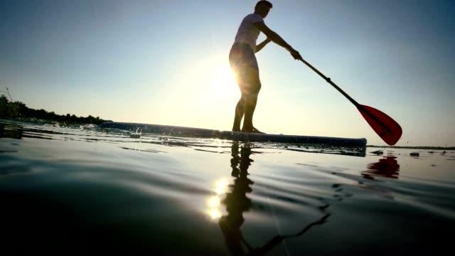 De stand-up paddleboarding SLO MO silhouet op het meer