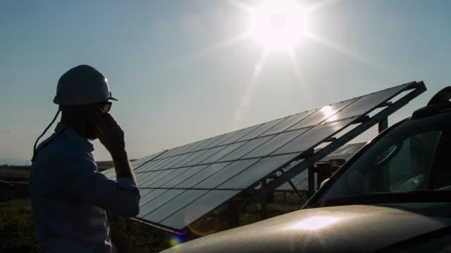Silhouette-Techniker Gespräch per Telefon unter Solarkraftwerk