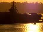 Silhouetted Boat Passes Navy Aircraft Carrier Deck at Sunset