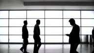 Silhouetted Businesswomen and Businessmen Walking