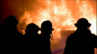 Silhouetted firefighters work to put a raging fire out.