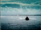 Silhouetted lifeboat moves through sea towards camera then turns out of shot England