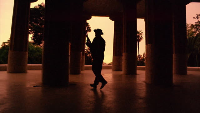 ORANGE silhouetted man holding guitar spinning between large columns / Parc Guell, Barcelona