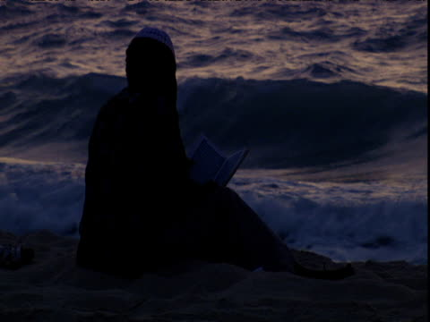 Silhouetted man reads from Koran while seated on sandy beach at dusk Dubai