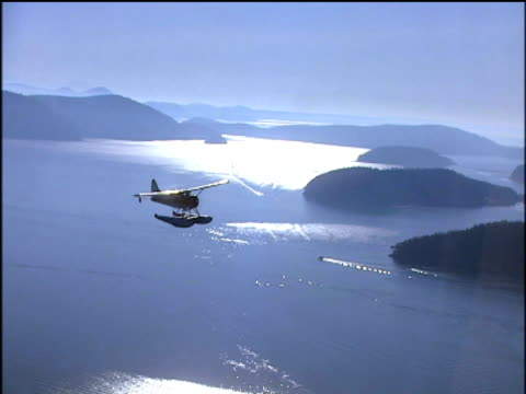 Silhouetted sea plane flying over San Juan Islands