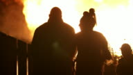 Silhouetted spectators watch as a bonfire constructed by a loyalist/unionist community as part of the 'Eleventh' celebrations furiously burns, Belfast, Northern Ireland.
