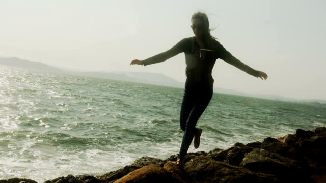 A silhouetted young woman jumps from rock to rock by the water.
