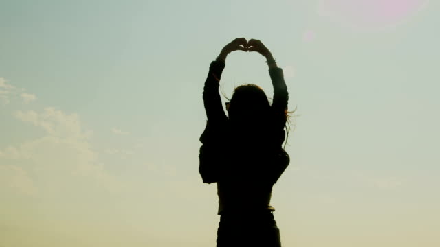 A silhouetted young woman raises her hands to the sky and forms a heart.