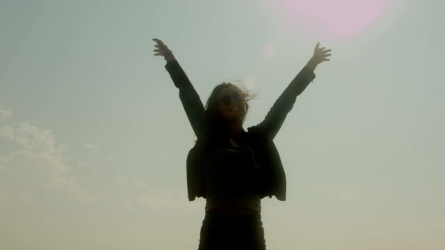 A silhouetted young woman raises her hands to the sky.