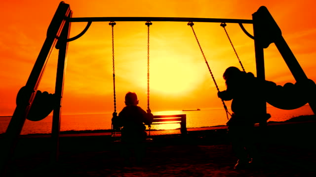 Silhouettes of children on a swing at sunset