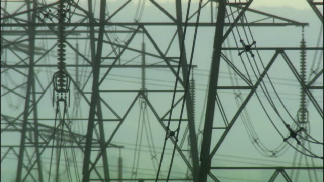 CU, Silhouettes of electricity pylons in field, United Kingdom