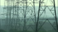 MS, Silhouettes of electricity pylons in field, United Kingdom