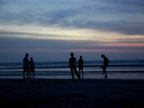 WS, Silhouettes of five men playing soccer on beach at dusk, Jericoacoara, Brazil