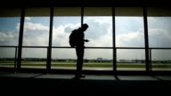 Silhouettes of man use cellphone in the Airport