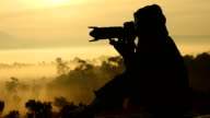 Silhouettes of Nature photographer in action,slow motion