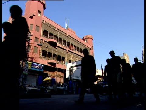 Silhouettes of pedestrians walking down a street in Pakistan