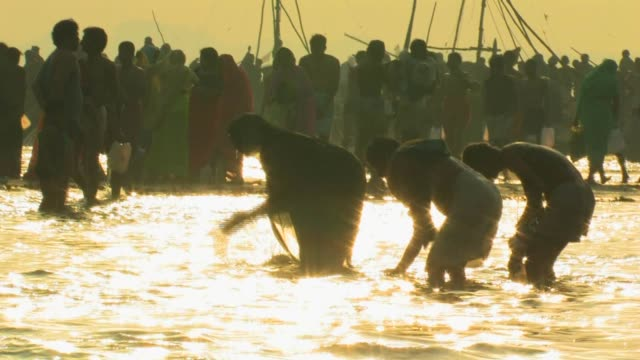 MS, Silhouettes of people performing ritual bath, Allahabad, Uttar Pradesh, India