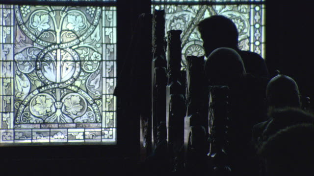MS Silhouettes of people sitting in front of stained glass window at Marburg's city hall / Marburg, Germany