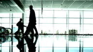 Silhouettes of People Walking in the Airport