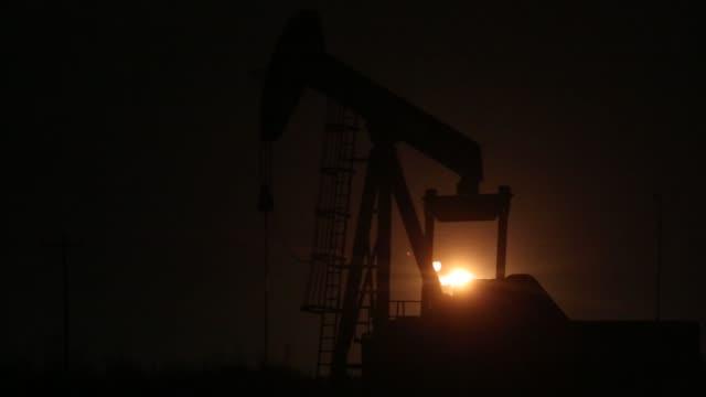 Silhouettes of pumpjacks in an oil field surrounding Midland Texas US on Wednesday Nov 8 2017 Photographer Luke Sharrett Shots full shot of pumpjack...