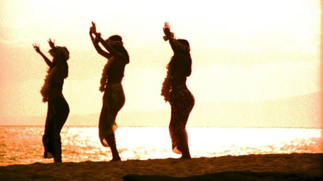 ORANGE silhouettes of three female hula dancers dancing in unison / ocean in background / Hawaii