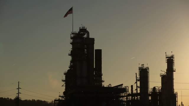 Silhouettes of towers and smokestacks of the Marathon Petroleum Corp's Catlettsburg Refinery are backlit by the sunset in Catlettsburg Kentucky US on...