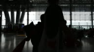 Silhouettes of travellers at airport