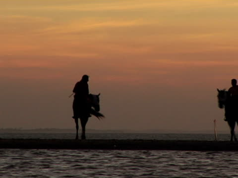 WS, Silhouettes of two horseback riders on Jericoacoara beach at sunset, Brazil