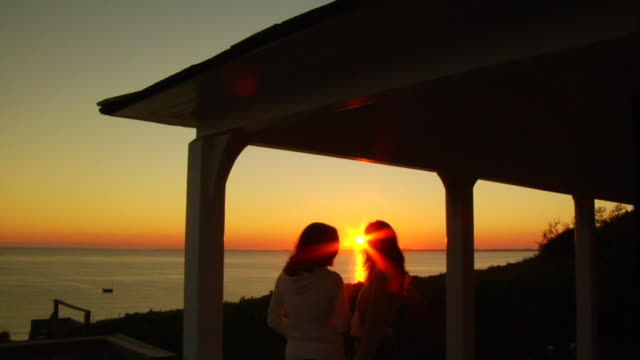 MS, Silhouettes of two women on porch facing ocean at sunset, rear view, North Truro, Massachusetts, USA