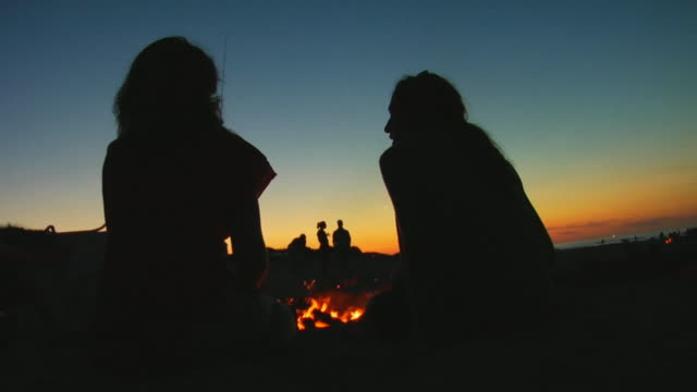 CU, Silhouettes of two women sitting at bonfire on beach at dusk, rear view, North Truro, Massachusetts, USA