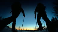 SLO MO LD silhouettes snowshoeing into sunset on mountain top
