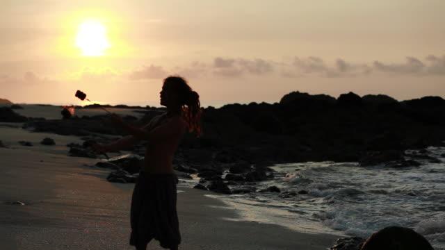 MS Silhuoette of rasta man spinning fire on beach with sunrised / Montezuma, Punteranes, Costa Rica