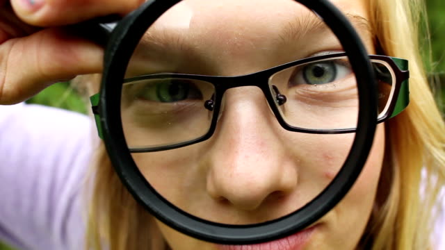 Silly girl with magnifying glass