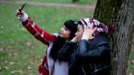 Silly young girlfriends taking a selfie leaning on a tree