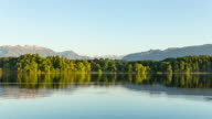 simple time lapse shot from the tiny camping island of Bernau located in the glassy Bavarian lake of Staffelsee on a beautiful sunny day - noon to sunset - glassy reflecting waters and blue sky