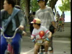 Singapore Families at Sentosa Resort SINGAPORE EXT People cycling along bike path in park / family sitting on blanket / woman and toddler eating...