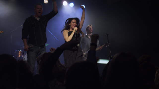 Singer and musicians performing on stage as audience dances / Spanish Fork, Utah, United States,