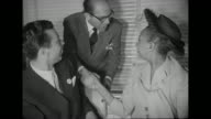MS singer Josephine Baker sits at banquet table with her husband Jo Bouillon and others NAACP banner hangs in background / MS Baker shakes hands with...