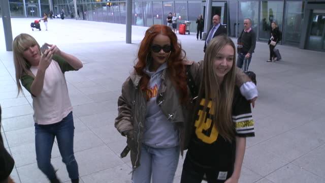 Singer Rihanna happily poses with teenage fans after arriving at Heathrow from New York where she had been making a TV appearance Casually dress in...