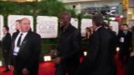 Singer Seal [Seal Henry Olusegun Olumide Adeola Samuel] walks down the red carpet holding camera at the Beverly Hilton Hotel