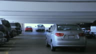 WS Single car driving away from camera through parking garage, Los Angeles, California, USA
