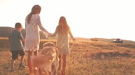 Single parent family walking with dog in field