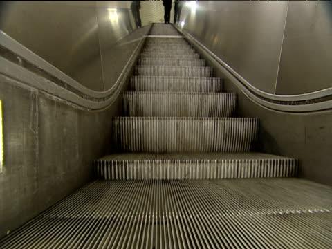 Single passenger rides U-Bahn escalator to top steps of escalators continue perpetual ascent Munich