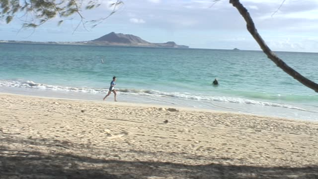 Single runners along ocean runs left to right