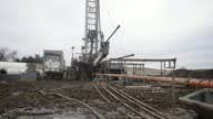 A single stack drilling rig stands at a Knox Energy Inc oil drilling site in Knox County Ohio US Four inch drill pipe sits in a tub at a Knox Energy...