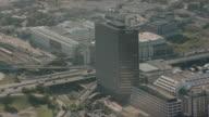 AERIAL Single tall building alongside freeway with clover leaf interchange