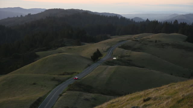 A single vehicle driving on a rural road at dusk.
