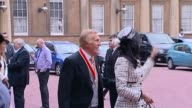 Sir Bruce Forsyth dies aged 89 T12101111 / EXT Forsyth and wife Wilnelia in the grounds of the palace after the investiture