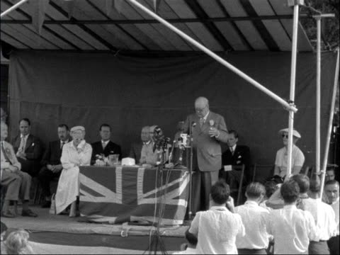 Sir Winston Churchill speaks at garden fete ENGLAND London Woodford Churchill on dais with others speaking SOT In its present form it has shown...
